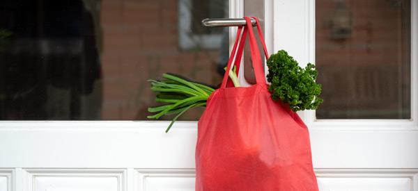 Nachbarschaftshilfe - Bild eines gefüllten Einkaufsbeutels der an der Türklinke hängt Copyright: Maren-Winter--Adobe-Stock